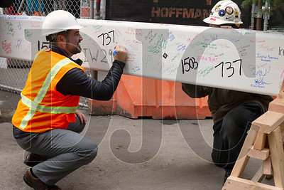 Joshua Dodson,  vice president of owner's represantative Day CPM, signs the beam.
