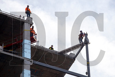 Ironworkers wait atop the structure for the beam to be lifted into place.