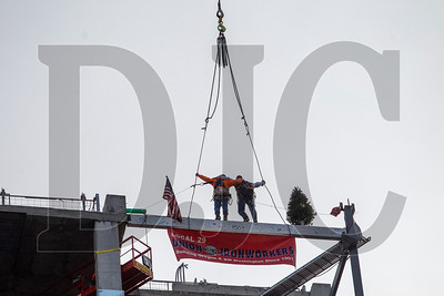 Ironworkers pose for a photo atop the beam to commemorate structural completion of the courthouse.