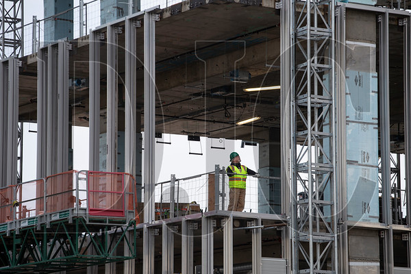 A worker on the buiding's tenth floor watches as the beam is set in place.