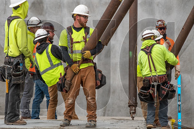 Todd Construction carpenter Thomas Holland holds a tilt wall brace as colleagues adjust other braces. (Josh Kulla/DJC)