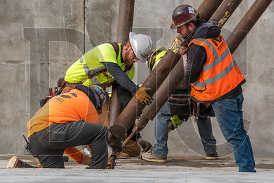Tyler Hutchison, lower left, and Shaun Julian, right, both journeyman operating engineers with Local 701 and employees of NessCampbell Crane + Rigging, help Todd Construction carpenter Thomas Holland, center, place a concrete tilt wall at Kellogg Middle School. (Josh Kulla/DJC)
