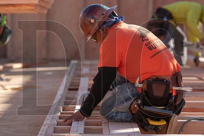 Mario May, a carpenter with Wood Mechanix, frames an interior wall. (Josh Kulla/DJC)