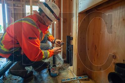 Jalen Tapani, an apprentice plumber with Tapani Plumbing, installs a wet vent in a ground-floor apartment. (Josh Kulla/DJC)