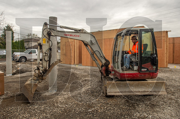 Last April, Charlie Hollingsworth cleared material from the edges of a footer of a tuck-under parking area at an affordable housing project in Northeast Portland. Portland is considering eliminating parking regulations for certain affordable housing projects. (Josh Kulla/DJC file)