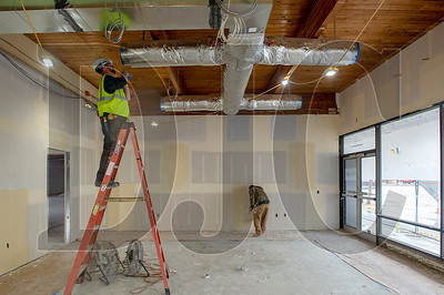 Mark McNeill, left, tapes off ductwork while Bridgeport Construction drywaller Ysidro Arellano applies joint compound to a wall at Oregon Tradeswomen, Inc.'s new headquarters space in Gresham. (Josh Kulla/DJC)