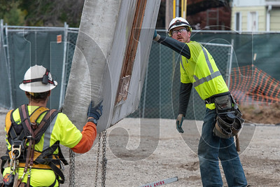Todd Construction carpenter Eric Seeski, right, guides a tilt wall into place at the Kellogg Middle School site. (Josh Kulla/DJC)