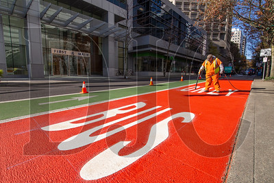 Portland Bureau of Transportation employee Vince Edmonson installs thermoplastic markings Wednesday morning on a new red bus lane on Southwest Main Street in downtown Portland. (Sam Tenney/DJC)