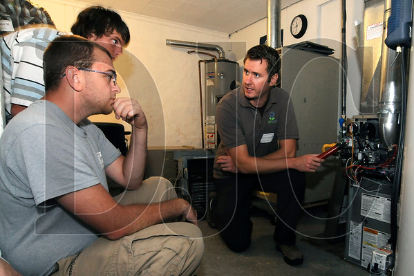 Portland YouthBuilders students Denis Sizman, top left, and Jeff Arneson, lower left, listen as Robert Hamerly, an energy efficiency specialist with GreenSavers USA, speaks about energy consumed by a home furnace during an energy audit demonstration on Sep. 30.  The audit was part of a Green Jobs Mentoring Day, which connected students from the Portland YouthBuilders program with contractors, workers and energy auditors to learn about jobs in green building and energy efficiency.