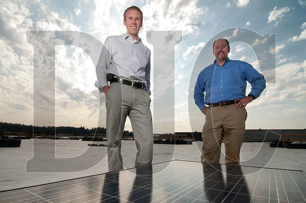 Andy Noel, left, the northwest regional manager at REC Solar Inc., and Jon Miller, the recently-hired director of REC's utility program, stand on the roof of the Fred Meyer Distribution Center in Clackamas, where the company is installing a 500 kilowatt system.