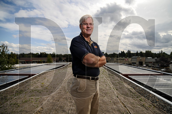 Bob Barman stands on the canopy of the new Chevron station in Beaverton that he owns with his wife, Katy.  The station features an eco-roof, a solar array, geothermal system, and a free electric vehicle charging station.