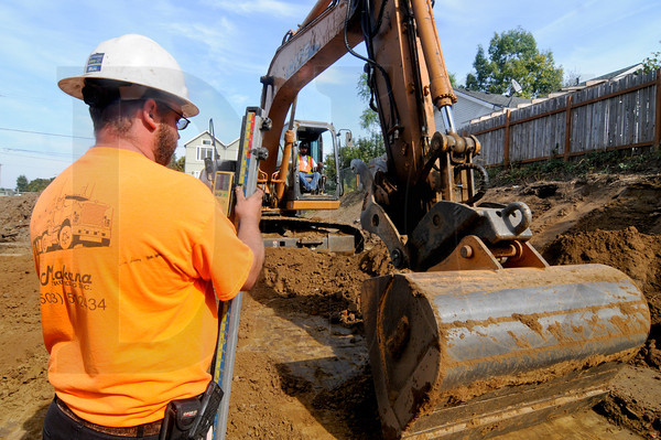 Tom Tackett, left, checks grade while fellow M&M Construction Services employee Tim Schmautz excavates sub-grade for a parking lot at a new mixed-use apartment project developed by Innovating Housing, Inc. in Northeast Portland. Ground was broken last week on the project, which is being built by Walsh Construction in partnership with Faison Construction.