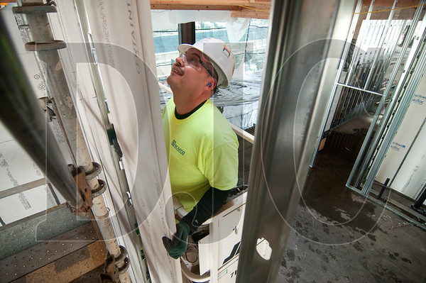Antonio Cuevas, a carpenter with EIS Local 146, hangs drywall in a second-floor stairwell.