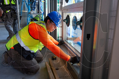 Primo Construction glazier Eloy Hernandez installs a window on the building's second floor.