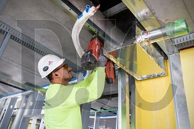Delta Drywall, Inc. carpenter Tony Del Cid frames a unit on the building's third floor.