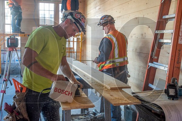 Burgener's Woodworking employees A.J. McKay, foreground, and Johnathan Hall, both journeyman carpenters with Local 1503, install cedar interior siding at The Redd East in Southeast Portland. (Josh Kulla/DJC)