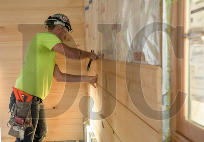 A.J. McKay, a journeyman carpenter with Burgener's Woodworking, installs cedar interior siding at The Redd East. (Josh Kulla/DJC)