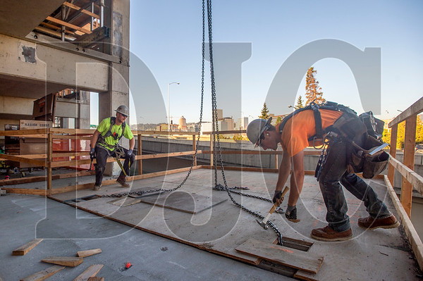 Hunter Fennimore, right, a journeyman carpenter with Local 271 and an employee of Marion Construction, disassembles a temporary platform. Aaron McGraw, a journeyman laborer with Local 737 and also an employee of Marion Construction, observes.