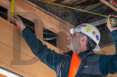 Peter Bandurovskiy, a journeyman carpenter with Burgener's Woodworking and a member of Local 1503, installs cedar interior siding at The Redd East in Southeast Portland. (Josh Kulla/DJC)
