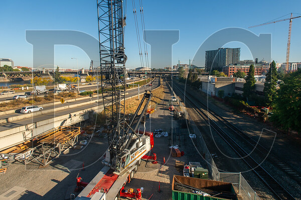 A mobile crane is being used for the project due to a constrained site bounded by Interstate 5 to the west and Union Pacific railroad tracks to the east.