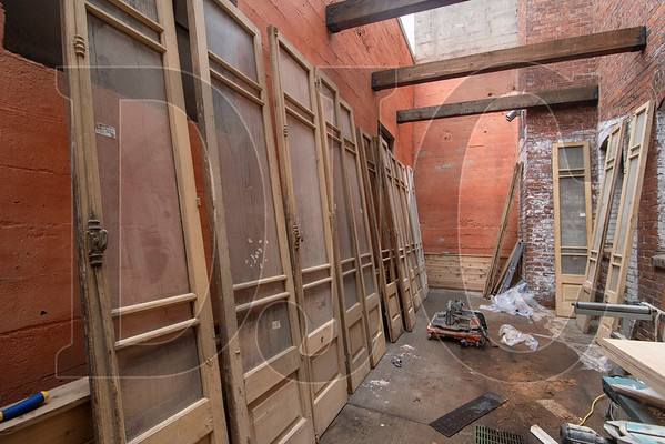 Original doors from the Vivian Apartments await refinishing in an outdoor courtyard space. (Josh Kulla/DJC)