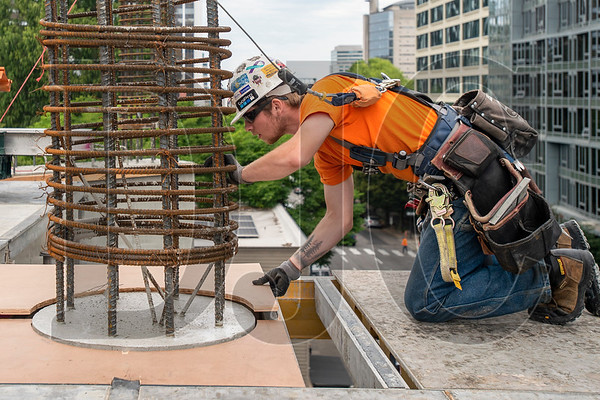 Justus Anthony, an apprentice carpenter with Local 1503 and Andersen Structures Inc., places a piece of plywood decking around the base of a concrete column. (Josh Kulla/DJC)