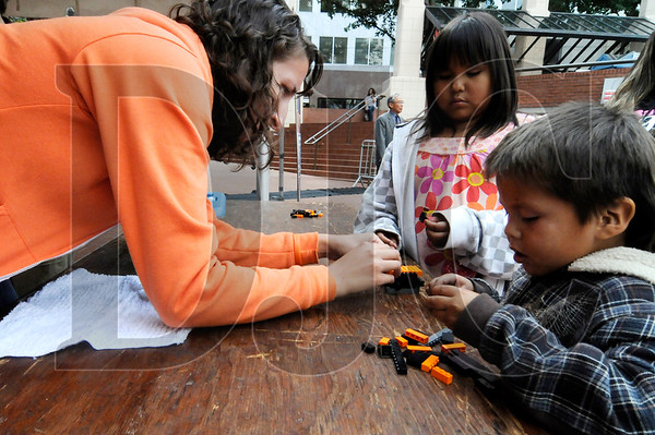 Robin Wagner, left, a bioengineering student at Oregon State University, helps Pearl Waubanascum, 7, and her brother, John Waubanascum IV, 4, make Lego sculptures to test in a wave machine Friday at Pioneer Courthouse Square.
