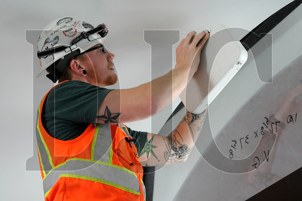 Sean Spriggs, an apprentice electrician with E C Company and member of IBEW Local 48, installs an emergency exit sign at the Virginia Garcia Memorial Health Center's Cornelius Wellness Center September 12. General contractor Bremik Construction is slated to complete the 12-month project in mid-October.