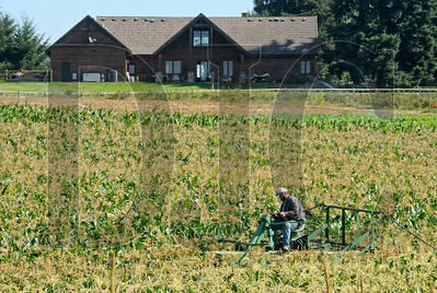 Doug Zimmerman, a partner in Bi-Zi Farms in Vancouver and son of farm owner Bill Zimmerman, sprays a crop for corn earworm Thursday morning. Farmers in Clark County are being squeezed into smaller spaces as planning efforts continue to support urban sprawl.