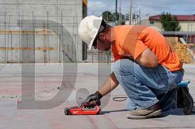 Sierra Construction Co. Inc. carpenter Robert Carrasco III uses a scanner to find anchor bolts in concrete September 10 at the Prescott Apartments, a $26 million project being built by general contractor Sierra Construction in North Portland.