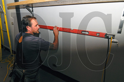 Robert Coté, owner of Robert Coté Construction, checks the level of a measurement while installing shelves at a new bar on East Burnside Street.