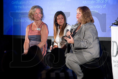 Carrie Hulse, left, of Business Oregon, and Eloisa Miller of the Office of the Governor listen as co-panelist Ruth Miles, a small business advocate with the Office of the Secretary of State, speaks during a panel talk.