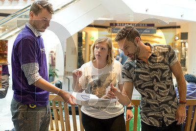 "Chris Stepovich, left, and Jess Dallas, center, both of HDR, and Kyle Elliott of Architectural Resources Group review plans for their team's structure, ""Son of Can."""