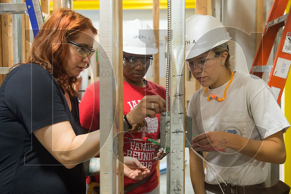 NECA-IBEW Electrical Training Center instructor Bridget Quinn shows Oregon Tradeswomen Inc. pre-apprenticeship students Uneka James (middle) and Elizabeth Applegate how to wire a light switch properly. (Josh Kulla/DJC)