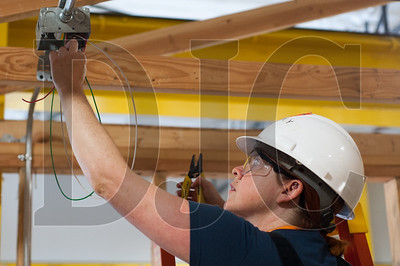 Oregon Tradeswomen pre-apprentice student Shannon Y works on installing an overhead light fixture during a recent class at the NECA/IBEW Local 48 Electrical Training Center. (Josh Kulla/DJC)