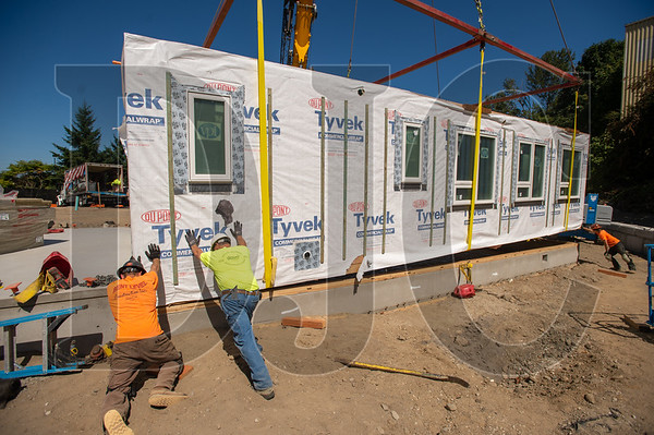 Crews set a modular unit in place atop a foundation. (Josh Kulla/DJC)