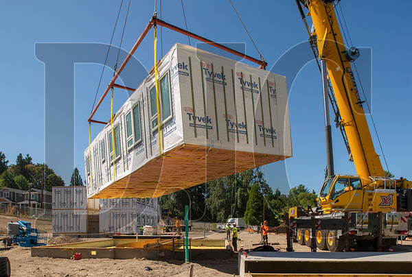 The first of four modular boxes is flown into place atop a concrete foundation at the LISAH project site. (Josh Kulla/DJC)