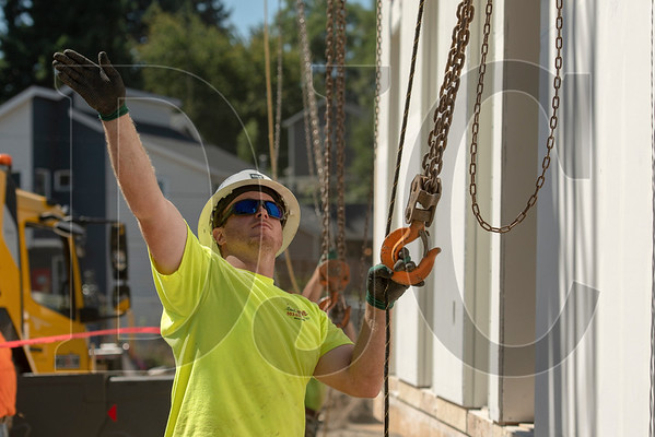 Cody Humphrey, foreman of a crew of laborers with Bent Level Construction, signals to a crane operator as a modular box is rigged. (Josh Kulla/DJC)