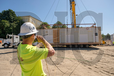 Cody Humphrey talks to a crane operator as he helps guide a modular unit into place. (Josh Kulla/DJC)