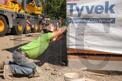 Darren Kilbourne, a laborer with Bent Level Construction, muscles a modular box into position. (Josh Kulla/DJC)