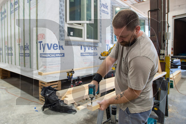 Carpenter Ben Jenkinson of Rockwood Cabinetry prepares strips of interior trim at the Mods PDX warehouse in North Portland. (Josh Kulla/DJC)