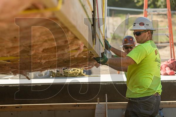 Cody Humphrey helps guide a modular unit into place. (Josh Kulla/DJC)