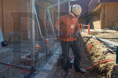 Mason Brittan, an apprentice electrician with AC&E Electric Company, cuts a section of conduit for the access control system in the school's new secure entry vestibule. (Josh Kulla/DJC)