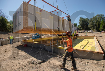 Bent Level Construction employee Brody Humphrey helps guide a modular box into place at the LISAH affordable housing development in North Portland. (Josh Kulla/DJC)