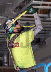Journeyman carpenter Jose Placencia, a member of Local 146 and an employee of Western Partitions Inc., constructs a ceiling grid. (Josh Kulla/DJC)