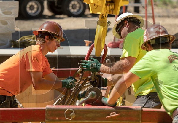 Bent Level Construction Employees, from left, Brody Humphrey, Cody Humphrey, and Darren Kilbourne prepare a steel rigging frame that will be used to lift a modular box into place. (Josh Kulla/DJC)