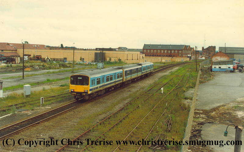 Class 150 3 Car Sprinter DMU number 150 143 passes Grimsby Docks.  This centre car of this unit was DMSL number 52205 from unit number 150 205.  Evidence of the former double track prior to the 1985 singling is still visible.<br /> 1989