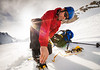 Mountaineer attaches crampons to boots, Aoraki Mount Cook National Park