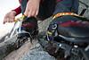 A mountaineer fastens crampons to boots. Tapuae-o-uenuku, Ka Whata Tu O Rakihouia Conservation Park