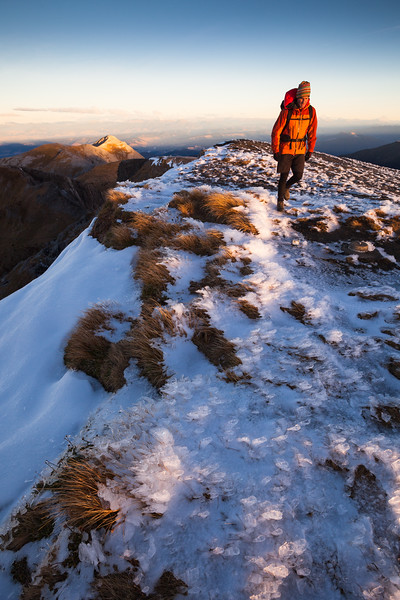 Male tramper walks on the summit of Mount Arthur, Kahurangi National Park